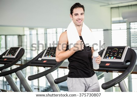 Smiling man on treadmill holding bottle of water at the gym - stock photo