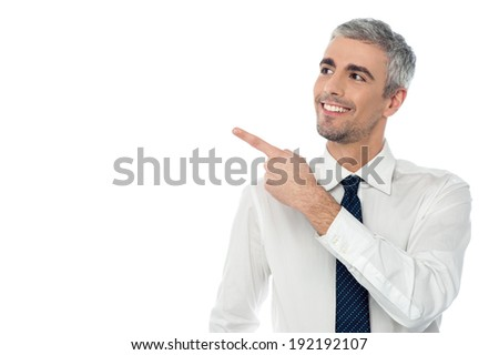 Smiling man pointing his finger towards something - stock photo
