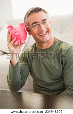 Smiling man posing with a piggy bank at home in the living room - stock photo