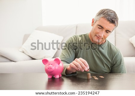 Smiling man putting some coins into a piggy bank at home in the living room - stock photo