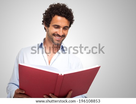 Smiling man reading a book - stock photo