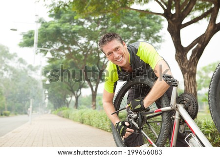Smiling man repairing his broken bicycle - stock photo