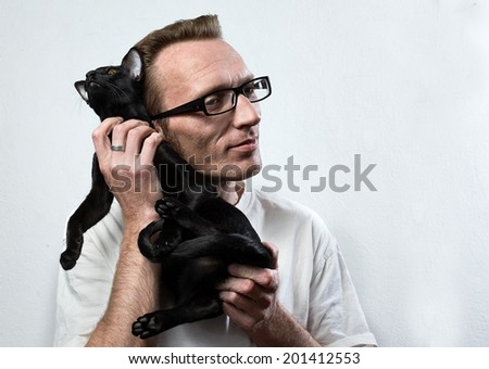 Smiling man rubs of a black frightened cat.  Relationship with animal concept.  - stock photo