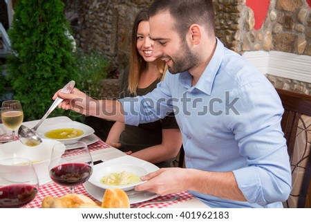 Smiling man serving soup while having lunch with his girlfriend in restaurant. - stock photo