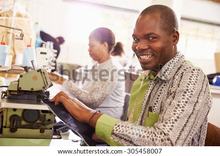 Smiling man sewing at a community workshop, South Africa - stock photo