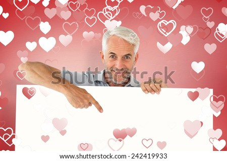 Smiling man showing large poster against red vignette - stock photo
