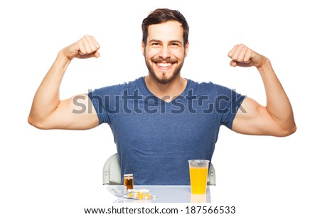smiling man showing muscles, having in front pills and orange juice, isolated on white - stock photo