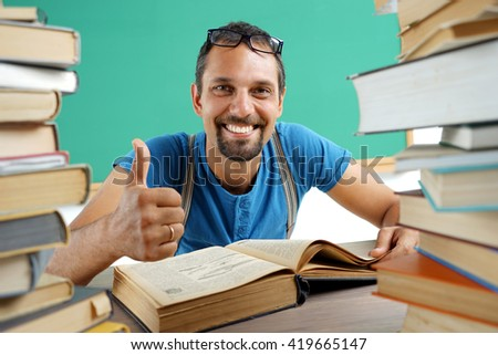 Smiling man showing thumbs up gesture. Photo of smiling teacher, creative concept with Back to school theme - stock photo