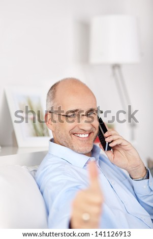 Smiling man showing thumbs up while calling at the telephone - stock photo