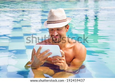 smiling man sitting in a pool with a tablet computer - stock photo