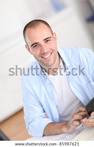 Smiling man sitting in office - stock photo