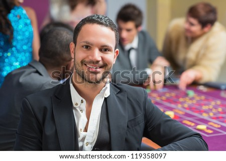 Smiling man sitting leaning on roulette table in casino - stock photo