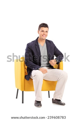 Smiling man sitting on a modern chair isolated on white background - stock photo