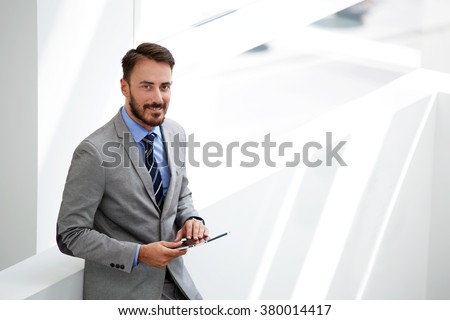 Smiling man skilled economist holding touch pad while standing in modern office interior near copy space,male entrepreneur using digital tablet while waiting beginning interview with new professionals - stock photo