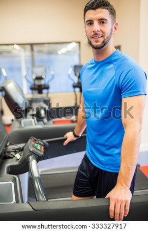 Smiling man standing on a treadmill at the gym - stock photo
