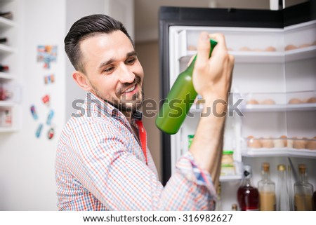 Smiling man taking out cool beer from fridge and looking at it - stock photo