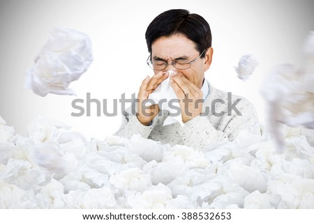Smiling man using a tissue against used tissues - stock photo