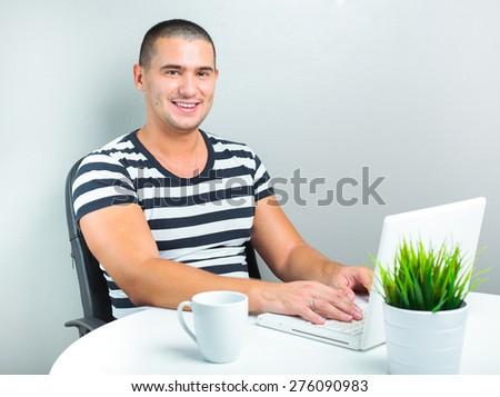 smiling man using his laptop - stock photo