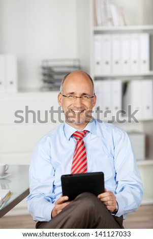 Smiling man using tablet at the office background - stock photo
