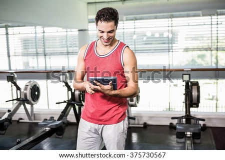 Smiling man using tablet in the gym - stock photo