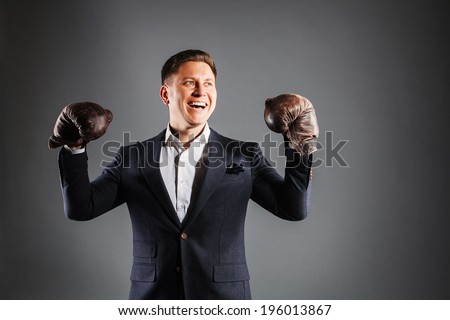 smiling man wearing boxing gloves raise his arms - stock photo