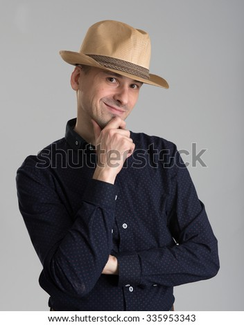 smiling man wearing fedora hat isolated over grey - stock photo