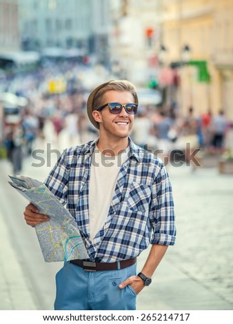 Smiling man with a map in the city - stock photo