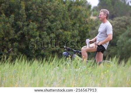 Smiling man with bicycle holding water bottle in rural field - stock photo