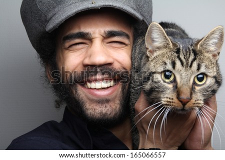 Smiling man with cat - stock photo