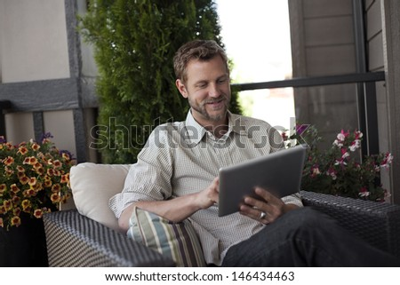 Smiling man with digital tablet sitting outside - stock photo