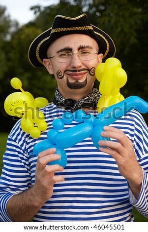 smiling man with drawed beard and whiskers in pirate suit with three air-balloons - stock photo