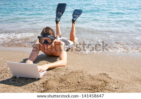 Smiling man with goggles and flippers lying on sand looking at laptop - stock photo