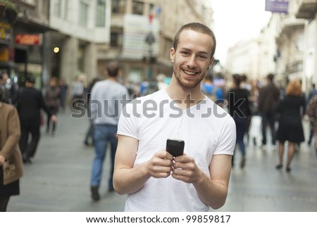 Smiling Man with mobile phone walking, background is blured city - stock photo