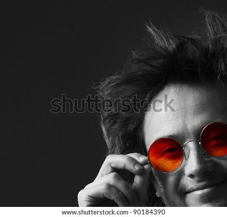 Smiling man with round hippie sunglasses and long hairs - stock photo