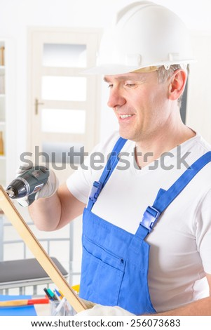 Smiling man with small, wireless electric drill wearing protective helmet - stock photo