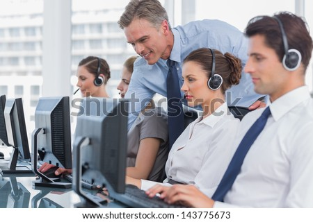 Smiling manager helping call centre agent with a headset - stock photo