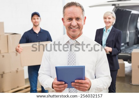 Smiling manager holding tablet in front of his colleagues in a large warehouse - stock photo