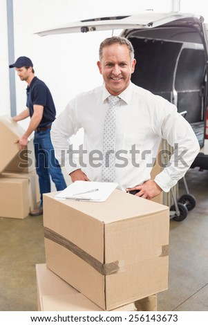 Smiling manager standing behind stack of cardboard boxes in a large warehouse - stock photo