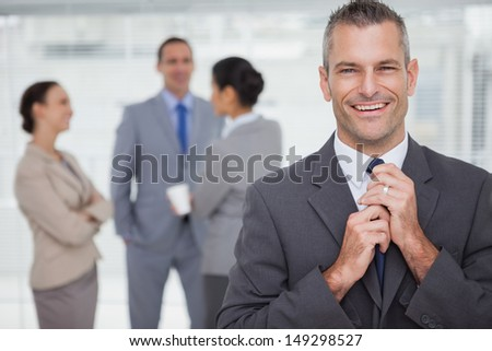 Smiling manager tidying his tie up with employees in background in bright office - stock photo
