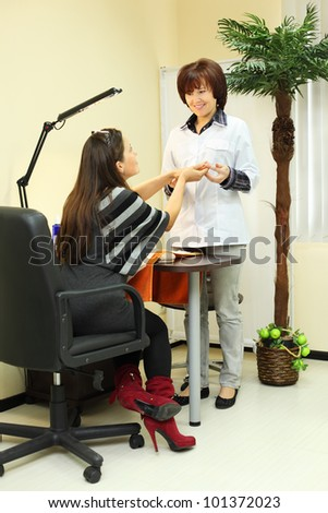 Smiling manicurist holds customer hands in beauty salon; client sits with her back to camera - stock photo