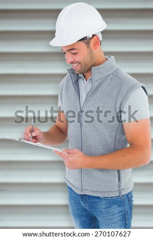 Smiling manual worker writing on clipboard against grey shutters - stock photo