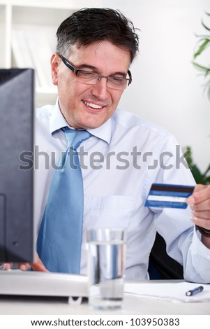 Smiling mature businessman holding credit card, online shopping - stock photo