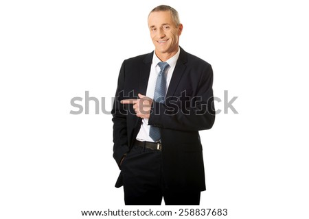 Smiling mature businessman pointing to the left. - stock photo