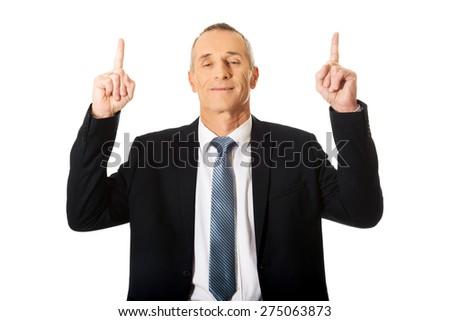 Smiling mature businessman pointing upwards.  - stock photo