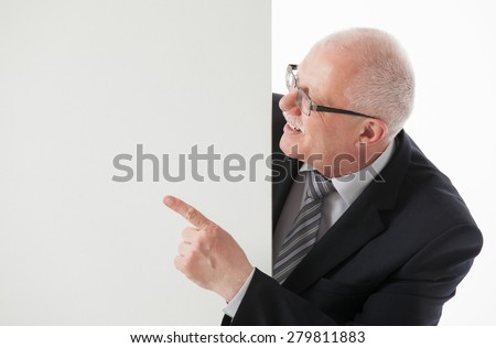 Smiling mature businessman showing something on white board, white background - stock photo