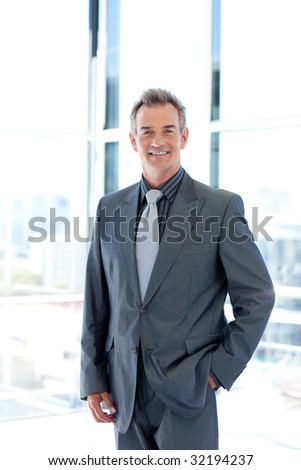 Smiling mature businessman standing in office - stock photo