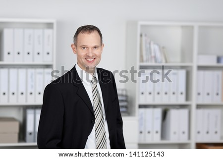 Smiling mature businessman standing over the office files background - stock photo