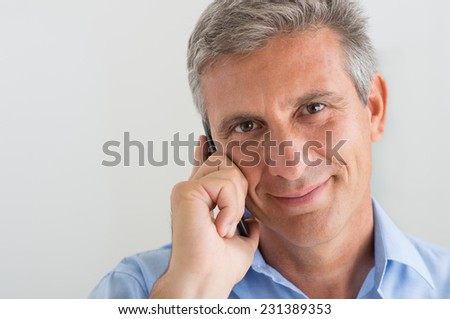 Smiling Mature Businessman Talking On Cellphone In Office - stock photo