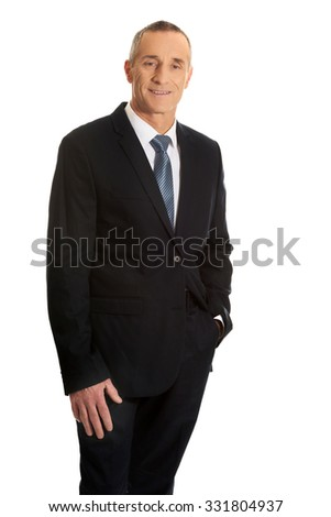 Smiling mature businessman with hand in pocket. - stock photo