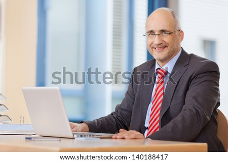 Smiling mature businessman with laptop at office desk - stock photo